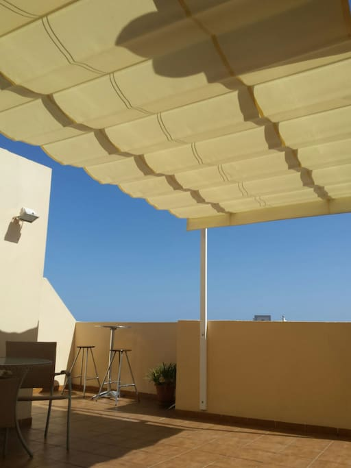 The private roof terrace with a lovely awning for shade .