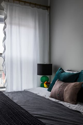 Master Bedroom with blackout blinds and soft draperies.