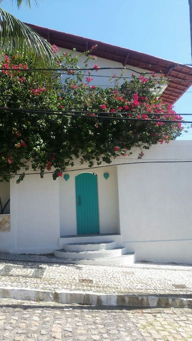 House entrance, with a beautiful Bougainville tree and turquoise door