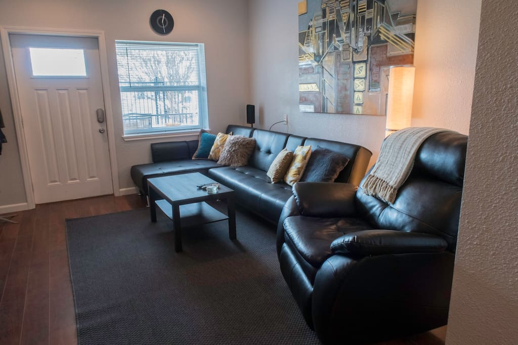 This inviting and spacious living room awaits your arrival. Features leather-comfortable chaise sectional and recliner seating with window view of Houston's downtown. For your extra guests, the sectional seating can be flattened and re-arranged to become a queen-sized sofa bed (not shown) that can fit up to 2 additional adults.