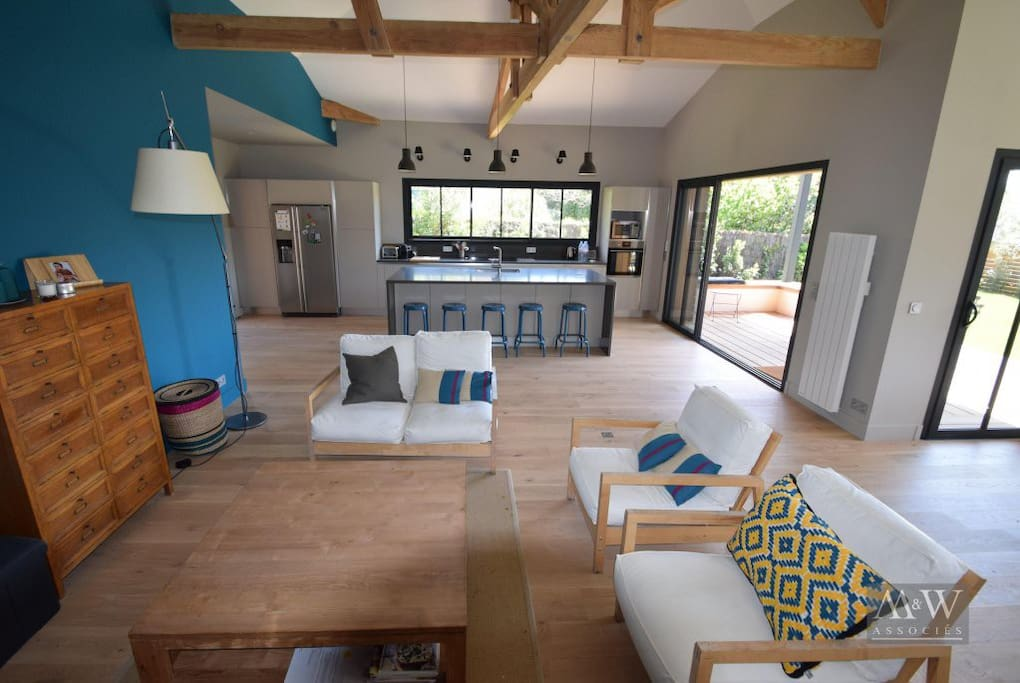 Coin salon avec vue sur le grand îlot de l'espace cuisine