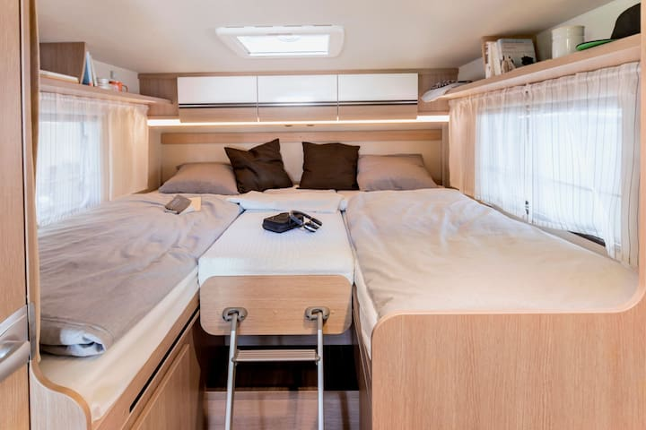 Two beds at the back of the camper. You can make it a king size bed by adding one more mattress.  This room can be shielded from the kitchen area by a door and/or curtains.