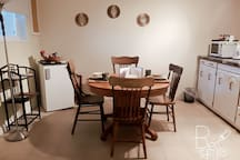 Eating area with microwave, coffee maker, kettle, fridge and large island for preparing.