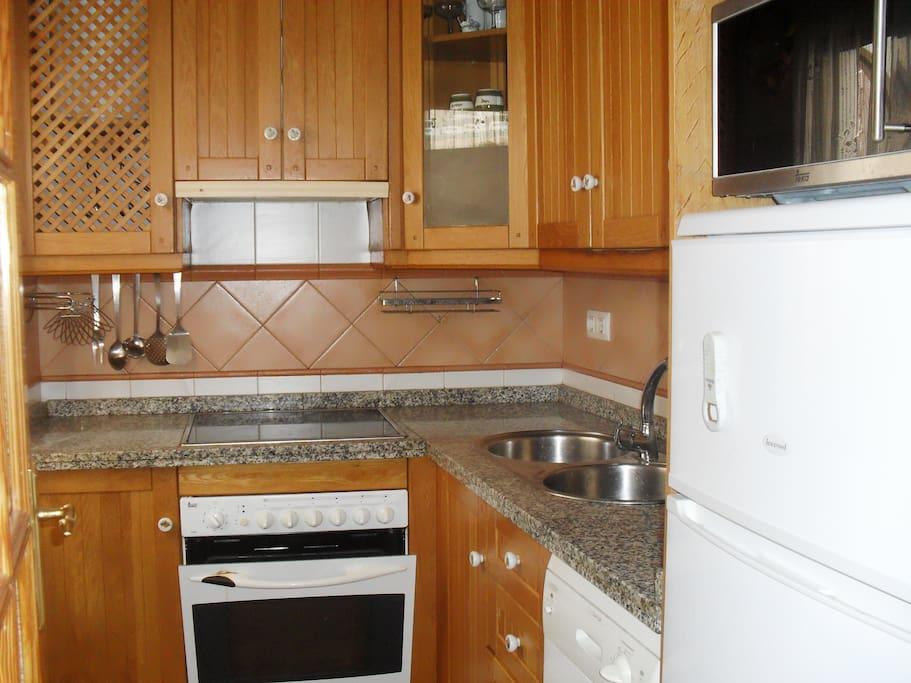 la cocina con ventana a la izquierda que da al patio consta de microondas horno, nevera y todo menaje para poder cocinar sin problemas