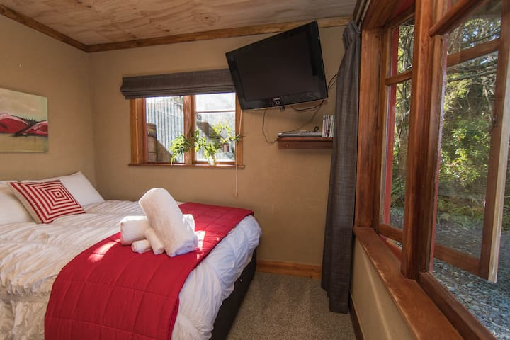 Children can enjoy watching a nature DVD on the lower floor, while the adults chat upstairs. This room is nestled in the forest, with a super comfy double bed and two singles (one trundler)