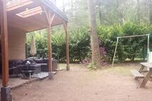 Heerlijke tuin met veel privacy, loungebank, ligstoel parasol, vuurschaal en speeltoestellen