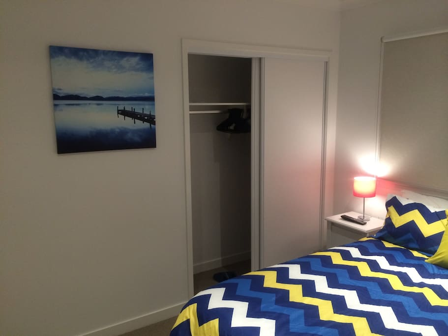 Scenic painting by side of built-in wardrobe. Hangers & bedroom slippers are provided.