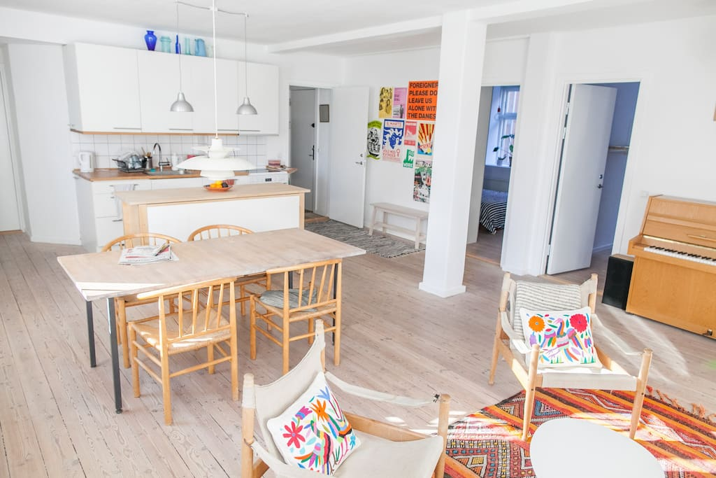 A view to the kitchen area, with plenty of storage place for food & snacks, the fridge off to the left, front door center, rooms off to the right.