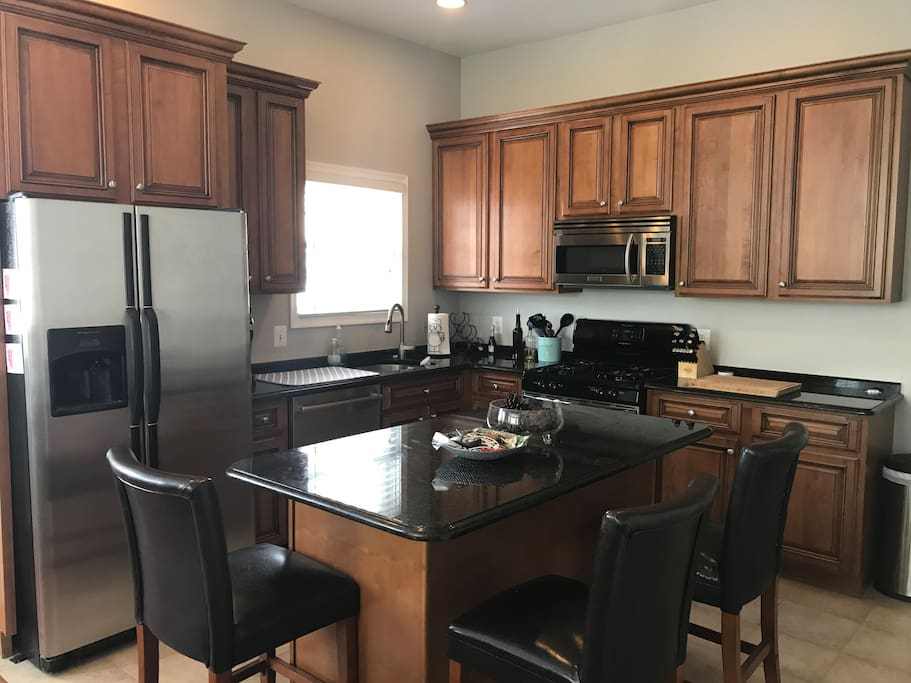 Modern kitchen, gas stove, stainless steel appliances and granite