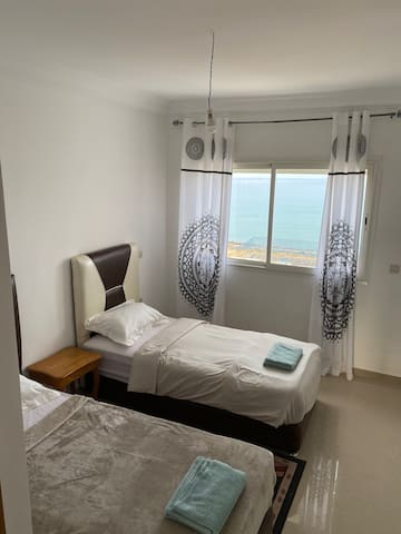 Second bedroom with two single beds and ocean view.