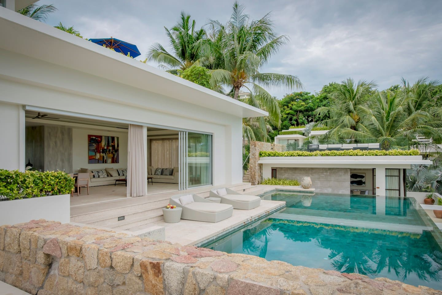 Air-conditioned lounge and dining area opening up onto an expansive pool deck