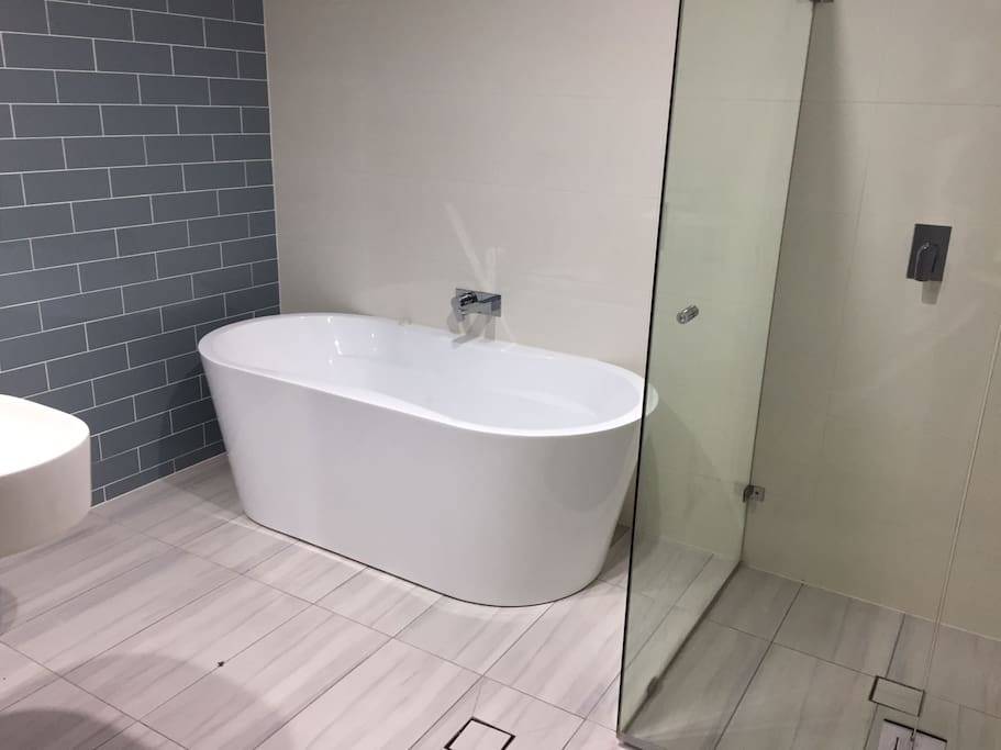 Ensuite bathroom with bath, shower and toilets. Clean and brand new