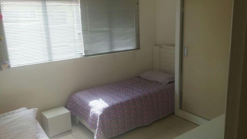 Quarto duas camas solteiro bem iluminado e limpo.