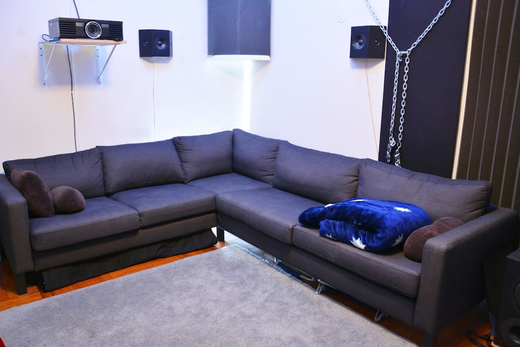 L-shaped Couch #1, soundproofing, surround sound speakers, and projector