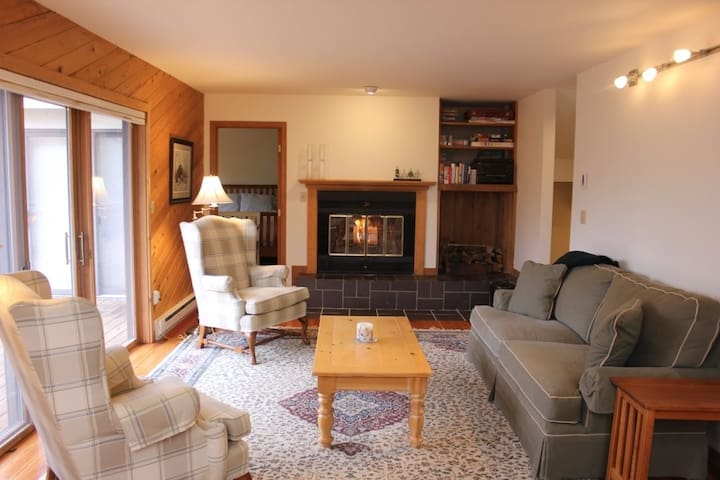 Living room with fireplace, sliding doors open to deck and views of Stratton Mountain, with main floor guest bedroom (bedroom #2) behind