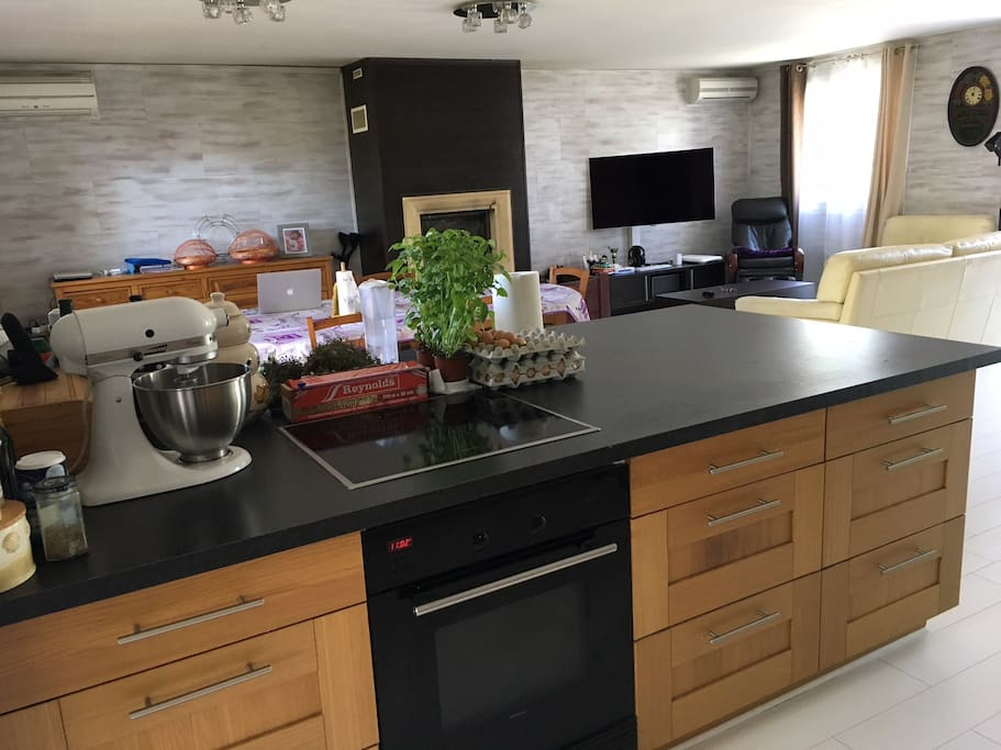 Salon spécieux accolé à une cuisine ouverte, accessibles aux visiteurs