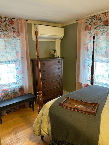 Second bedroom features a queen, a dresser, a bench, bedside table with lamp, closet with hangers and extra linens, and an individual  heating/cooling unit.