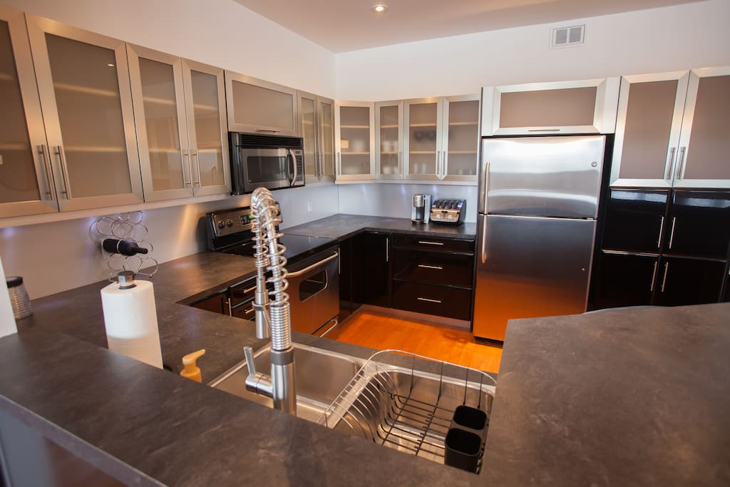 Large modern kitchen with side counter and four stools