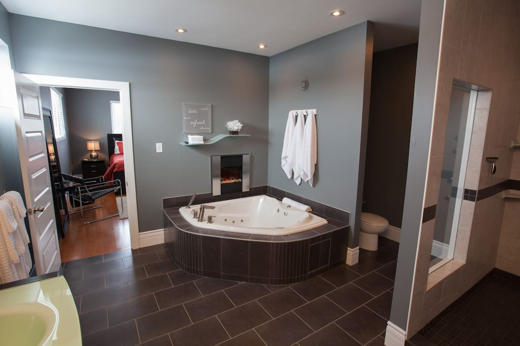 Luxurious and massive en suite with step-in shower, large tub with built-in electric fireplace