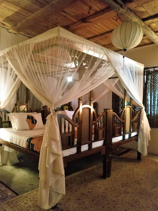 We've pushed two Zanzibari beds together under a giant net to make a bed fit for a...Sultan!