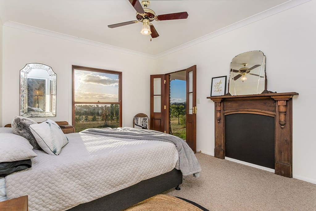 Bedroom 2 with red cedar french doors that open onto the back verandah, beautiful westerly views over the hills