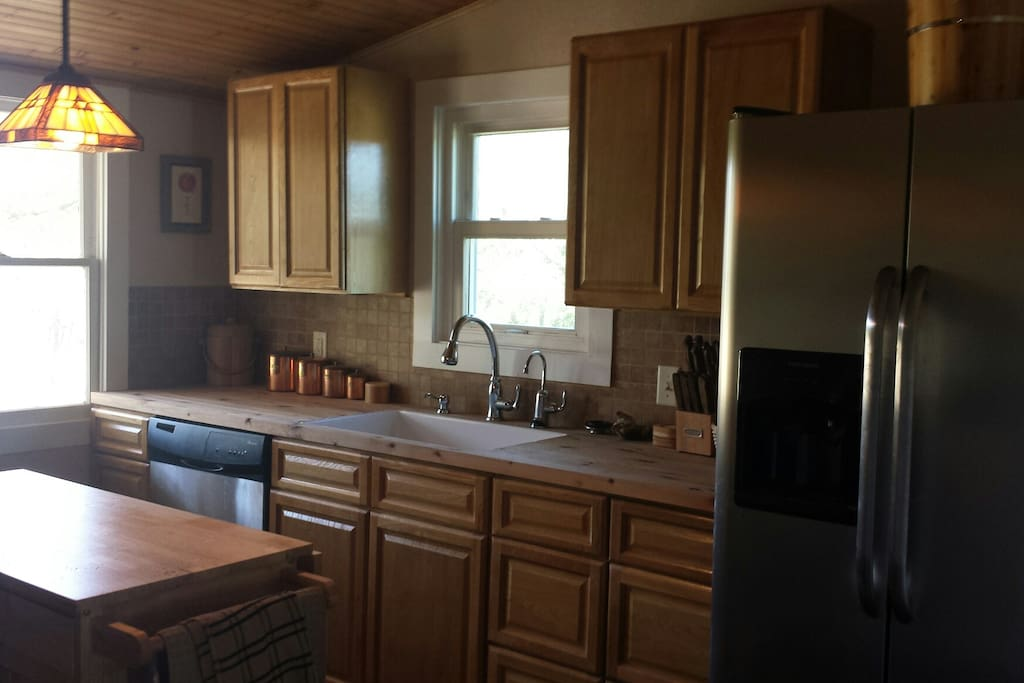 Remodeled kitchen with refrigerator, garbage disposal, dishwasher, stove and oven, microwave, pantry, coffeemaker, and toaster.