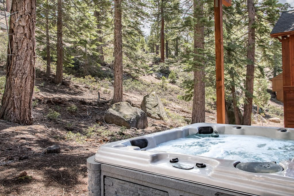 Soak in the bubbles beside the forested hillside.