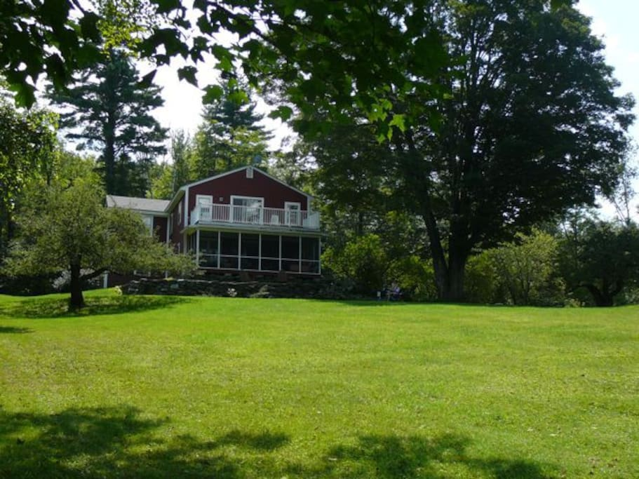 back of house; screen porch and sundeck and long green lawn