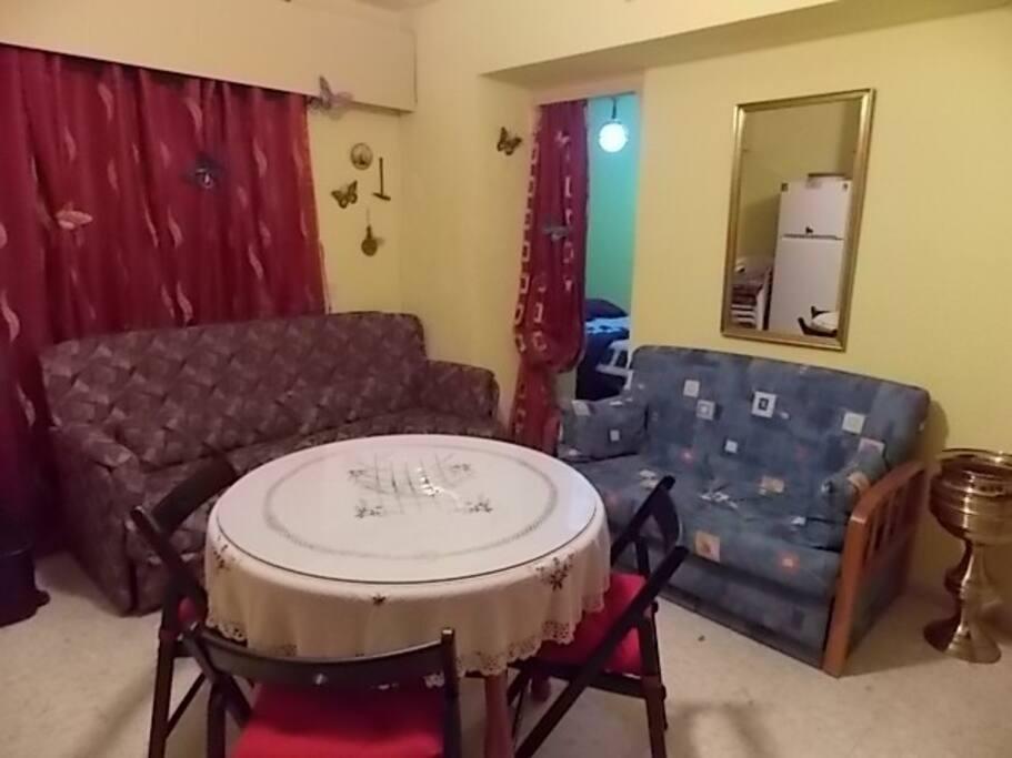 Petit canapé 1 place - Table ronde avec 4 chaises avec coussins .