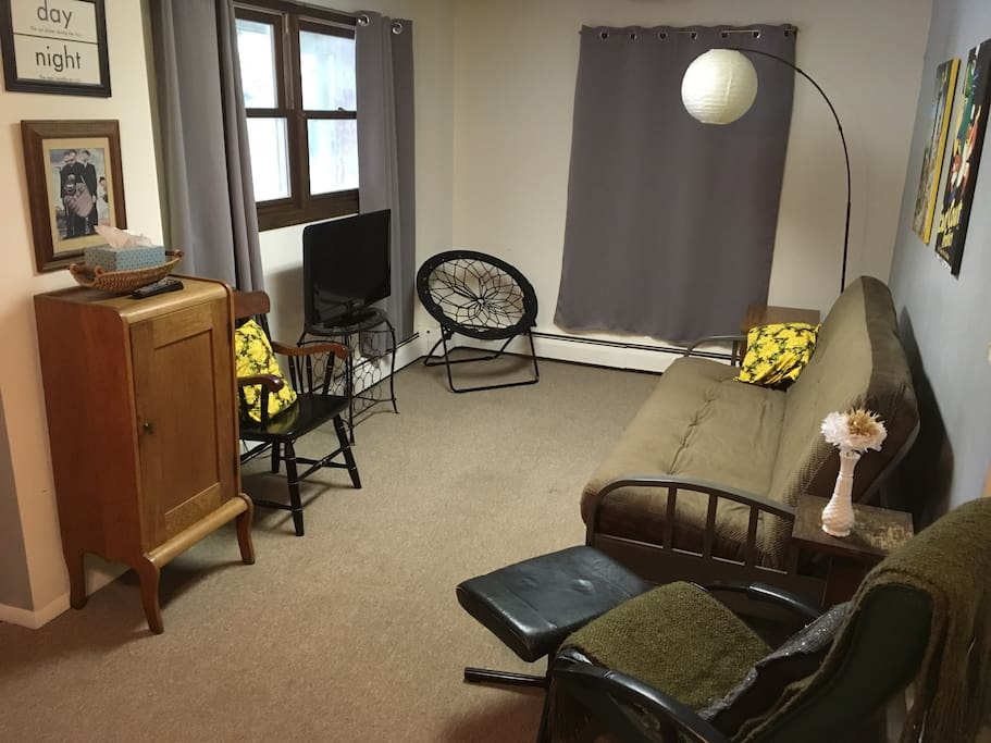 Living room with ample seating, outdoor lighting, and a futon with available bedding. We have a TV available however no cable access, bring your portable Roku, Google Play, or Apple TV and connect to the internet to stream.