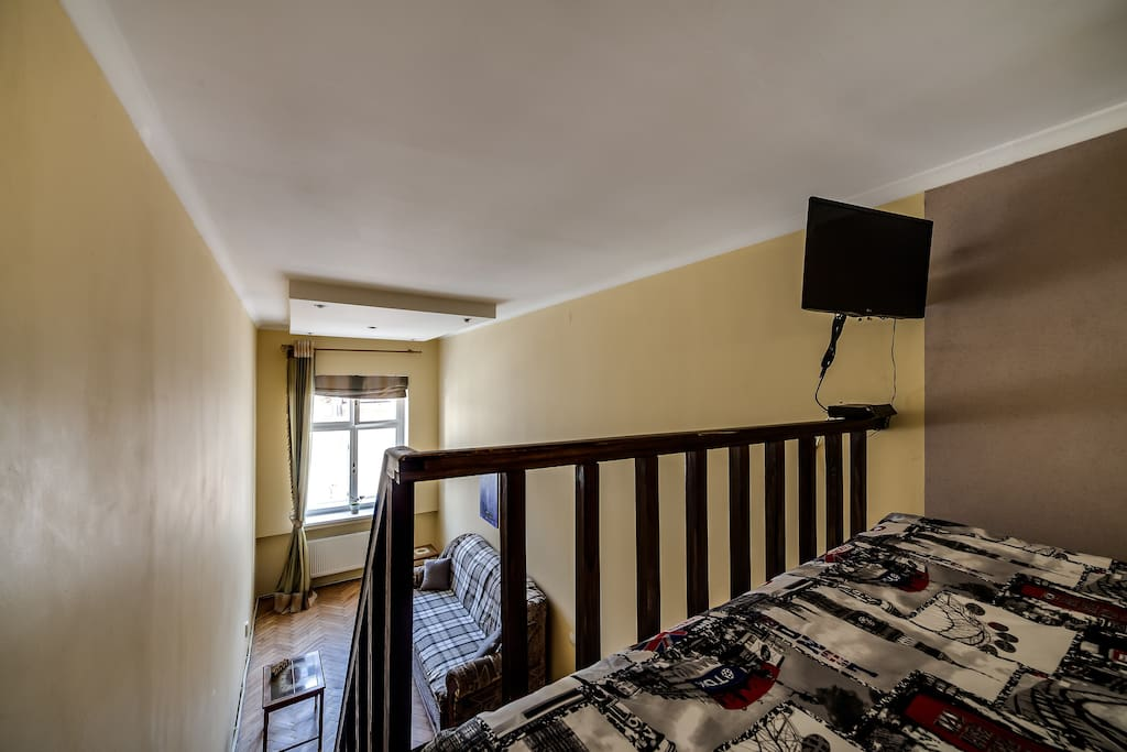 View of the room with sofa from the entresol where the mattress bed and TV are located