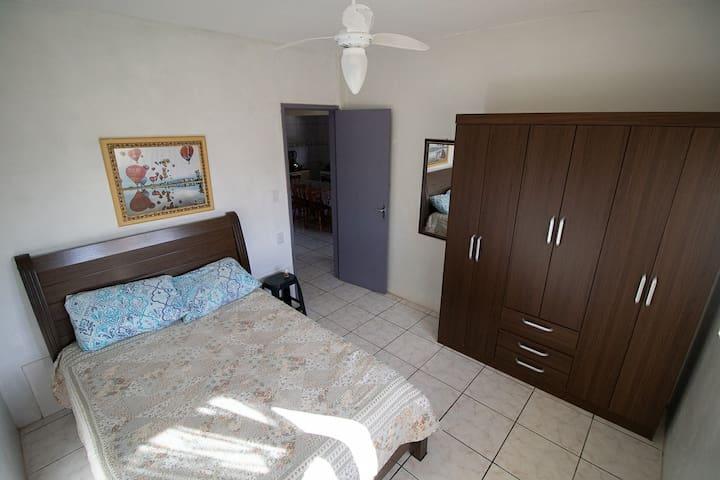 Quarto 1  Quarto completo com:  Cama de casal com 2 travasseiros Roupas de cama Lençol Cobertores  Ventilador de teto e de chão  Espelho  1 roupeiro 6 portas