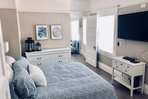 Bedroom with queen size bed and TV with cable. Doorway accesses dinning room.