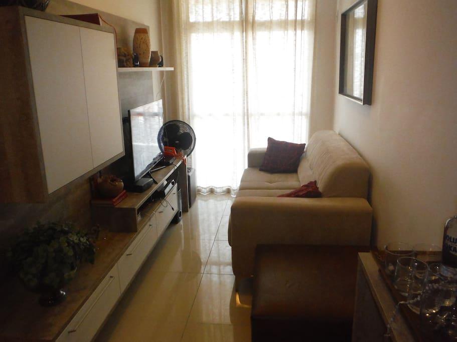 Sala de jantar com sofá, televisão LED Smart TV e TV a cabo.