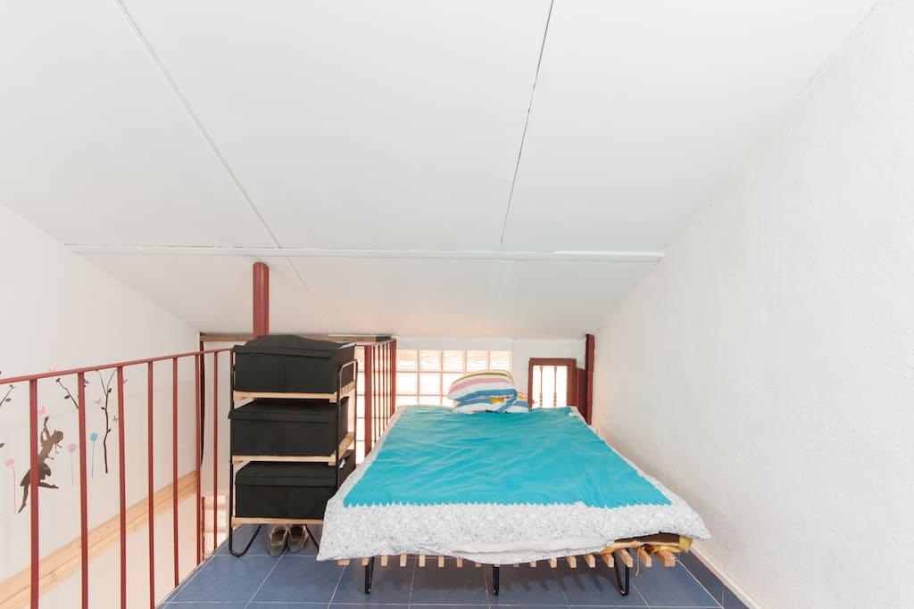 Dormitorio con cama doble en buhardilla