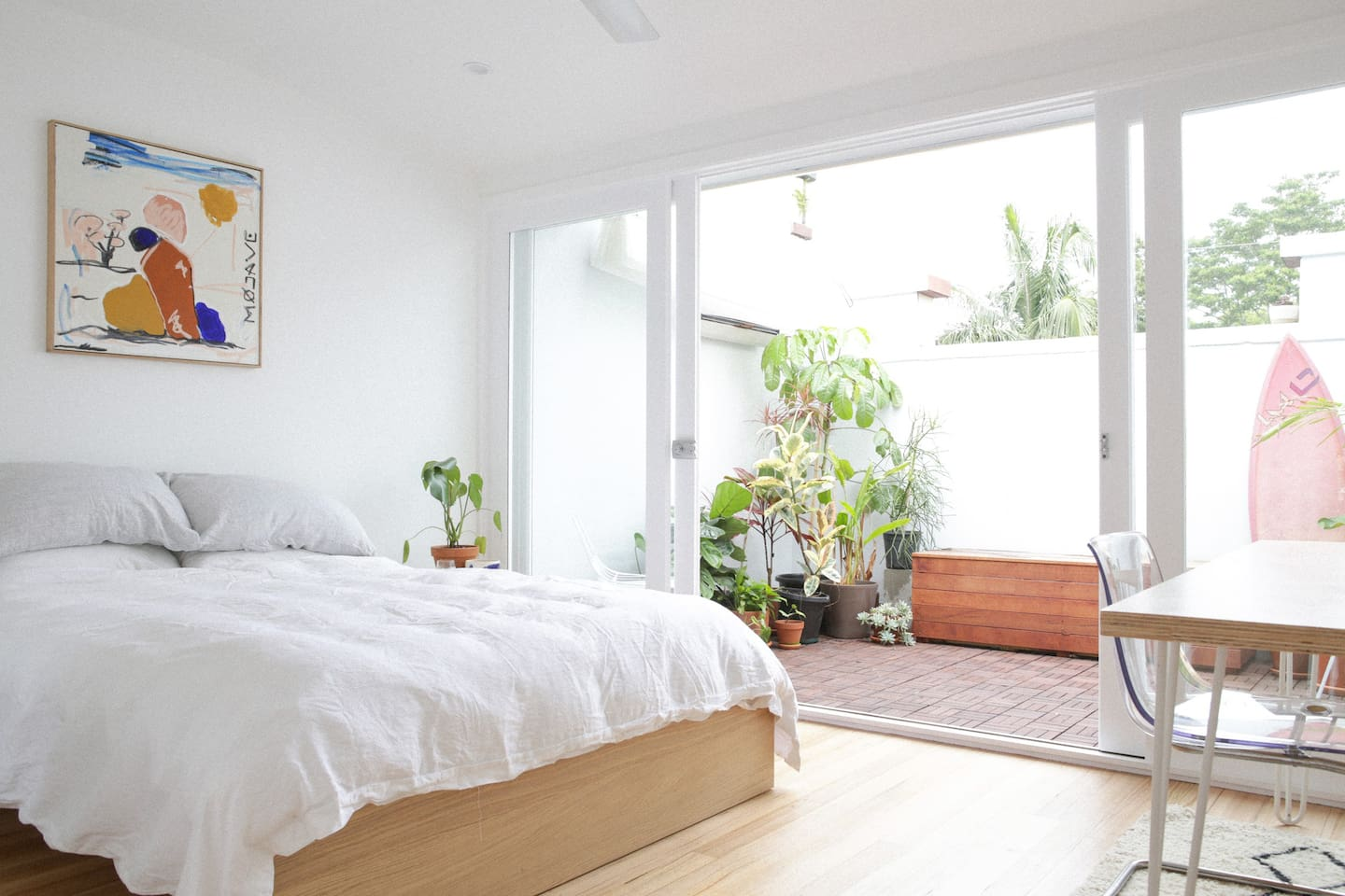 Spacious and light bedroom opens up to a plan filled private terrace overlooking the street below