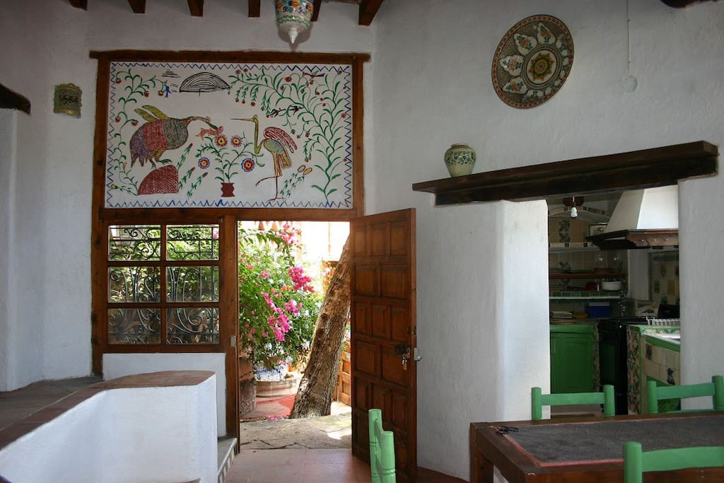 After passing the small garden you enter the living room on the right you can see the kitchen. You can see the beautifull otomi mural painted on the wall