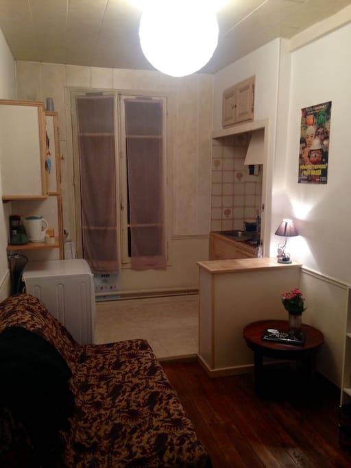 le salon, et la cuisine derrière, de nuit