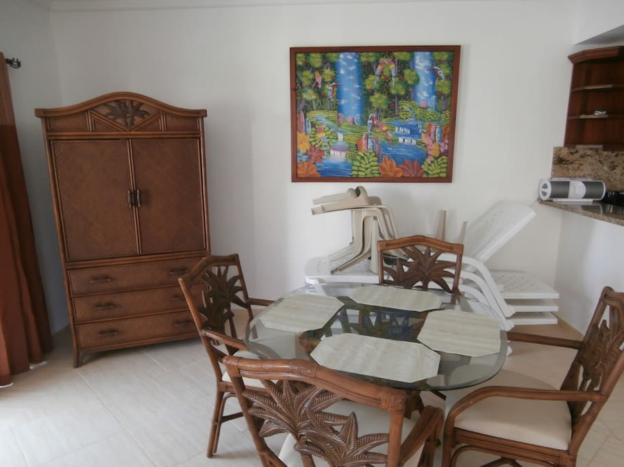 The dining area is open to the kitchen and balcony. There's enough outdoor furniture for everyone to be comfortable.