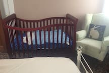 Well-made crib with cozy chair for nursing moms.