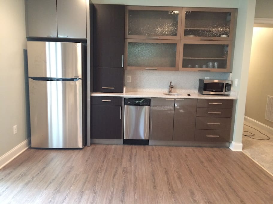 Brand new wet bar with modern garage door cabinets, fully stocked with dish and cookware.  Dishwasher, microwave, full sized fridge, coffee maker and induction burner.