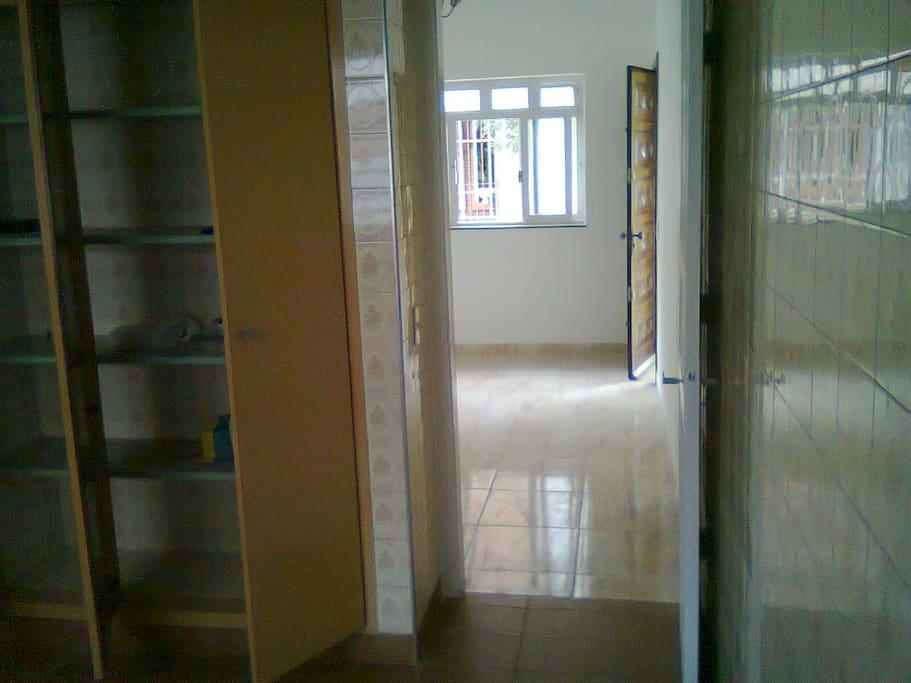 Ampla cozinha com armário embutido e uma sala confortável com claridade.s