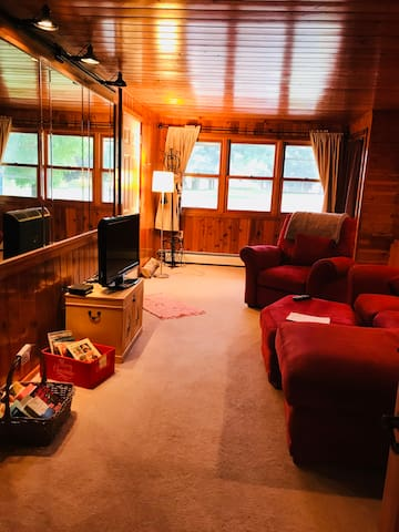 Private very cozy living room with couch with chaise lounger, a recliner and TV. The room is brighter than it appears. Windows let in light and open for a breeze. Room also has room darkening curtains. The cedar on the walls give it a cottage feel.