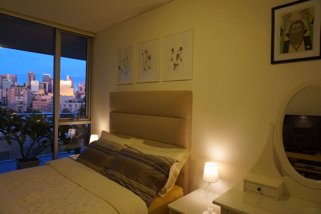 Your guest room at sunset.  Sun reflects off city buildings.