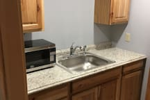 New fully equipped kitchen with birch cabinets, microwave, fridge and storage. Coffee pot, toaster. electric frying pan and electric hot plate.