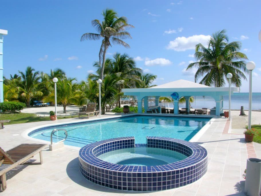 View of pool with gazebo and waving palms in background