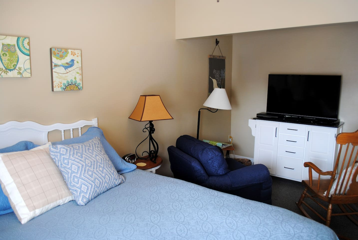 The master bedroom features a queen bed, dresser and sitting area with TV and DVD.