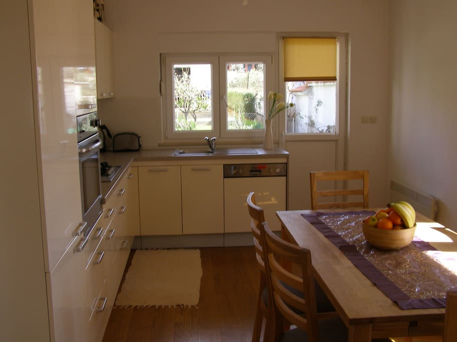 dining room and fully equipped kitchen with doors to back yard with terrace and BBQ