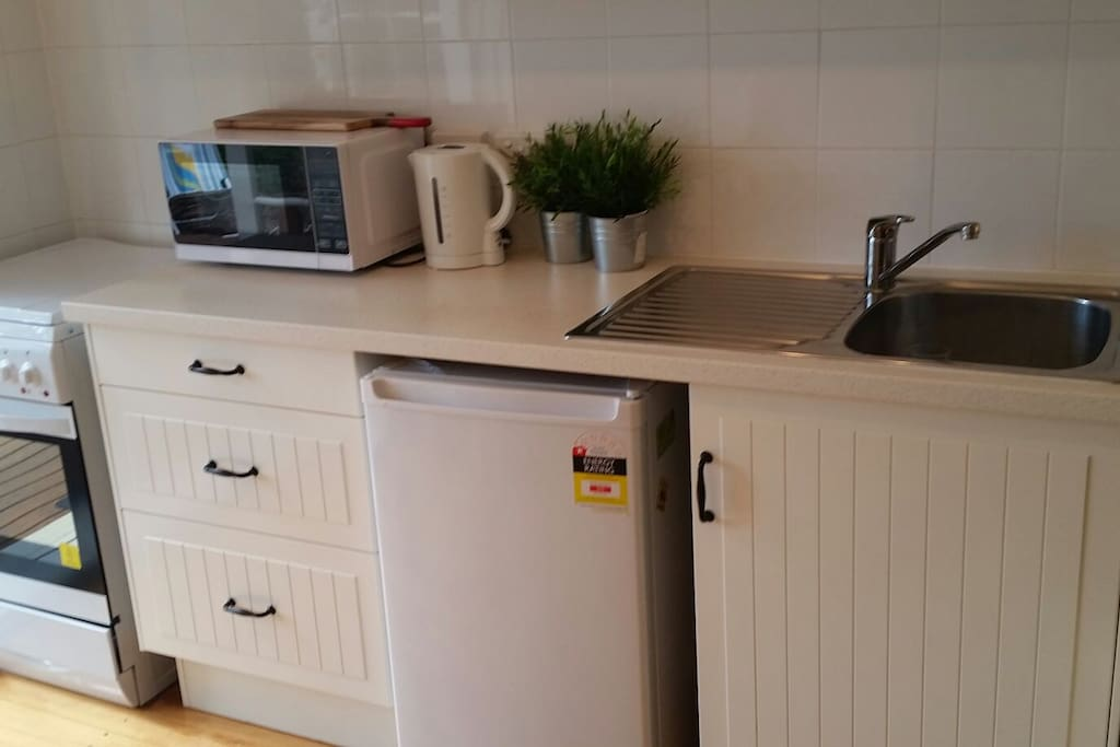 Kitchen has full size oven and stovetop microwave, kettle , toaster