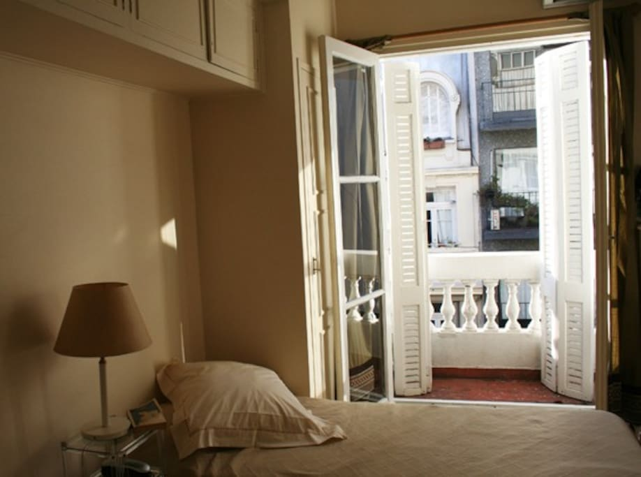 Bedroom with small balcony overlooking Arenales Street